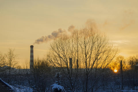 The factory pipe smokes against the background of a red sunset フォト