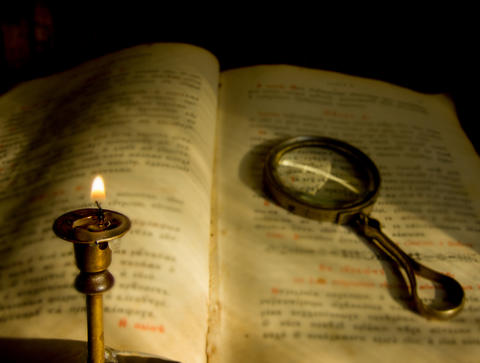 a dying candle and an old prayer book with a magnifying glass フォト