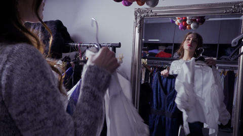 Young beautiful girl looks at the mirror and choosing clothes for special event Footage