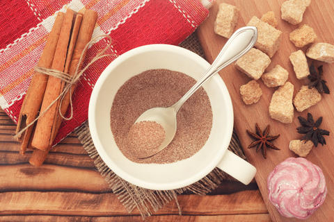 Cacao coffee powder in cup with cane sugar, zephyr and cinnamon sticks Photo