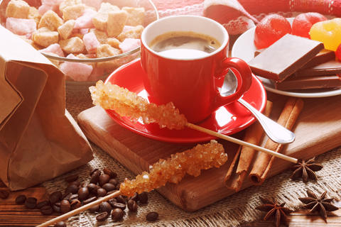 Red cup of coffee with cane sugar sweeteners, coffee beans and other sweet food Photo