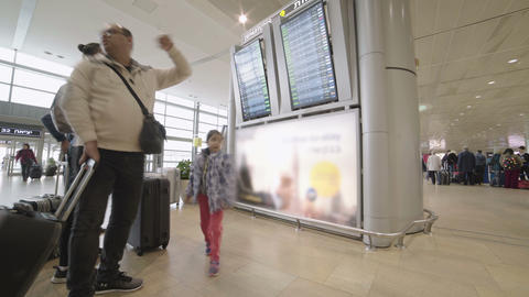 passengers at an airport terminal looking at departures board Footage