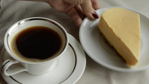 Two coffee and two plates with cheesecake a woman prepares a delicious Breakfast Live Action