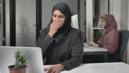 Girl in black hijab sits in the office and coughs, a disease, a cold, an illness Footage