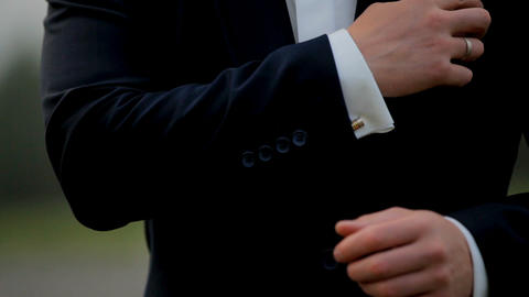 A young man in black suit adjusts his cufflinks of white shirt. Indoor. Close-up Footage