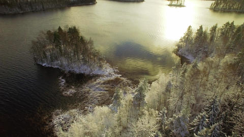 Small island and bay with first snow at a Nordic lake. Aerial shot Footage