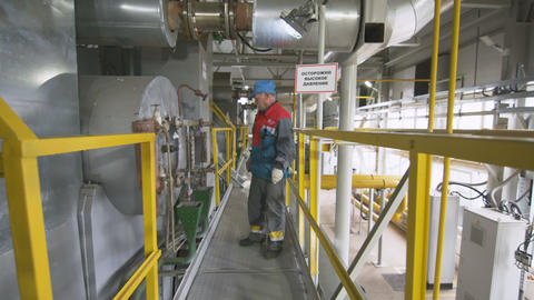 Worker Examines Equipment Gives Command with Nod Live Action