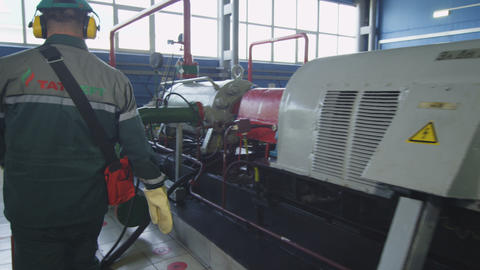 Worker Walks around Modern Operating Compressor 영상물