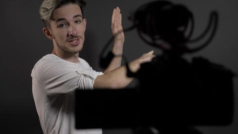 Happy confident young man filming himself in a professional studio and talking Footage