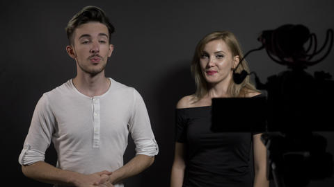 Young attractive man and woman recording video blog about latest trends on Live Action