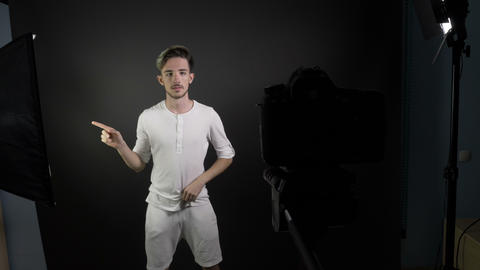 Young man fixing his hair and clothes before shooting video behind the scenes Footage