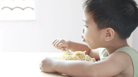 HD footage of Asian boy with fork in hands eats pasta, close-up Footage