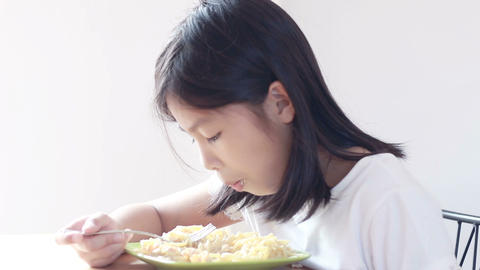 HD footage of Asian girl with fork in hands eats pasta, close-up Footage