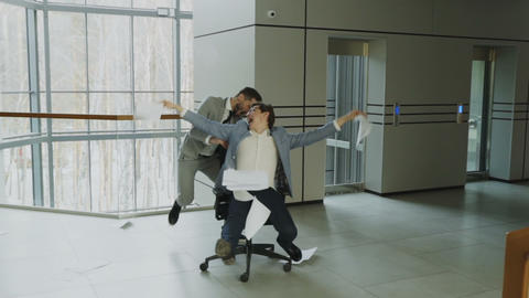 Slow motion of Two crazy businessmen riding office chair and throwing papers up Footage