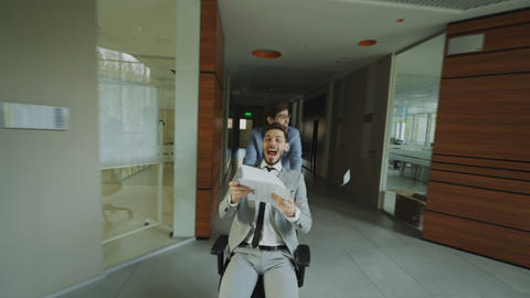 Dolly shot of Two crazy businessmen riding office chair and throwing papers up Footage