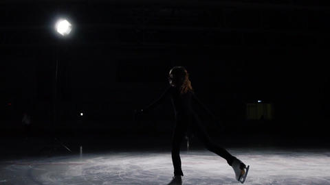 A professional woman, figure skater to a black suit at the competitions in Footage