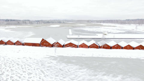 Flying over wooden red boathouses towards frozen river mouth. Time-lapse shot Footage
