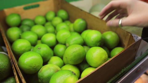 Young woman choosing fresh green limes in a supermarket picked from organic farm 影片素材