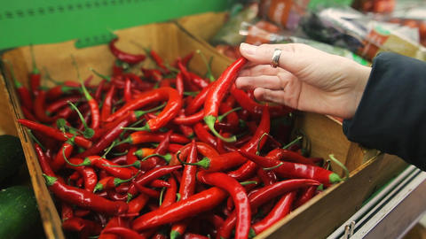 Young attractive girl chooses red hot chili pepper in the grocery department of Footage