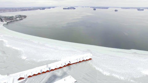 Freezing lake landscape with row of red boathouses Footage