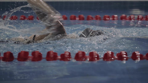 Female professional swimmer turning underwater on swimming pool close up Live Action