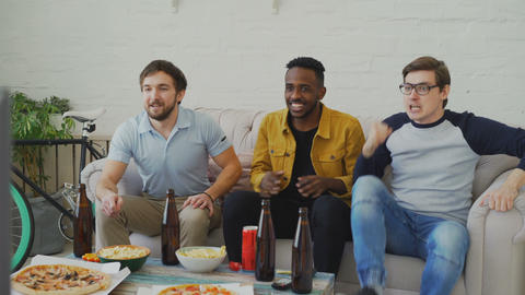 Group of young male friends watching sports match on TV together while drinking Footage