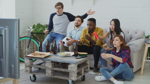 Multi-ethnic group of friends sports fans watching football championship on TV Footage