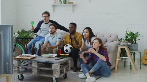 Group of young friends watching football game on TV together eating snacks and Footage