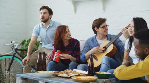Happy young friends have party at shared apartment and singing together while Footage