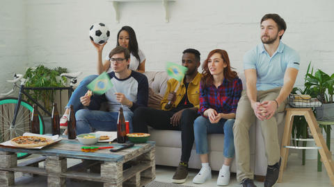 Multi-ethnic group of friends sports fans with Brazilian flags watching football Live Action