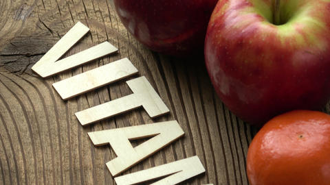 Fruit with inscription VITAMIN on brown wooden surface background Footage