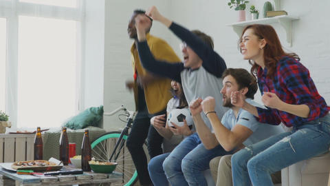 Slow motion of multi ethnic group of friends sports fans watching sport match on Live Action