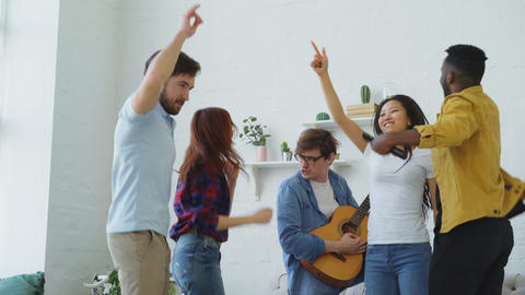 Group of multi ethnic friends dancing while young man playing guitar and having Footage