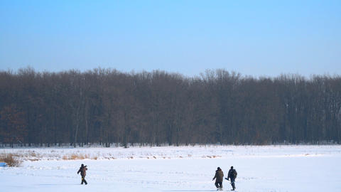 Group of men walk along the snow-covered ice of the lake Footage