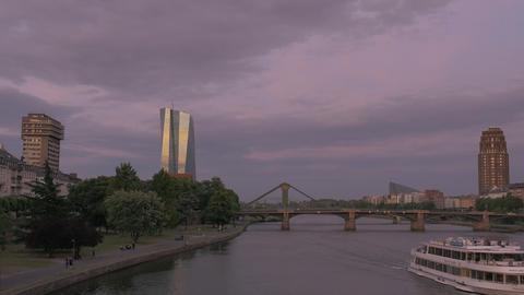 Frankfurt skyline after sunset with boat in Main river and violet color scheme ภาพวิดีโอ