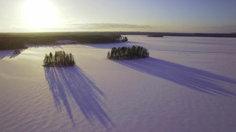 Flying over islands with long shadows at frozen lake Footage