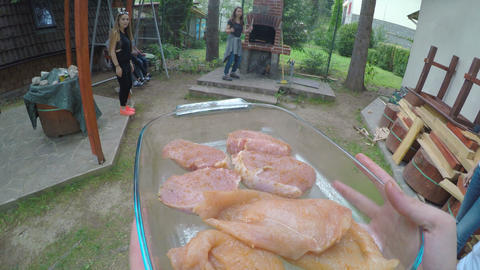 POV of host bringing raw meat preparing grill for barbecue party with cheerful Live Action