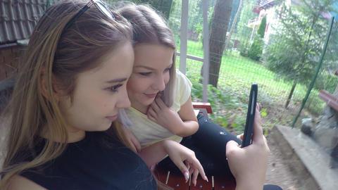 Teenage female friends chilling on swing in backyard doing funny selfies pics Footage