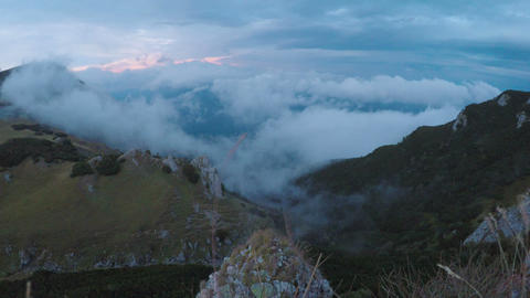 Spectacular cloudy landscape with mountains and misty alpine forest at sunset Footage