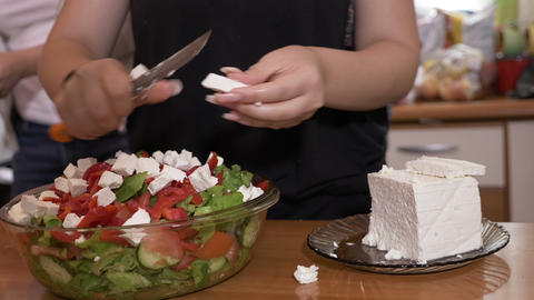 Female hands cook adding cheese to tasty healthy salad prepared in bowl while Footage