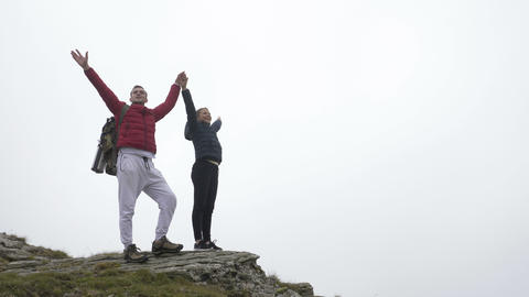 Cheerful teenage couple celebrating with raised hands reaching the summit Footage