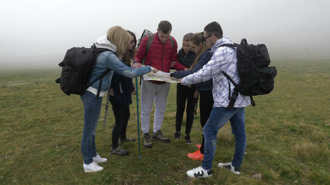 Group of lost young tourists hiking looking for direction trough fog reading the Footage