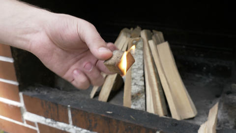 Man lighting up wood piece preparing bonfire outside for cooking Footage
