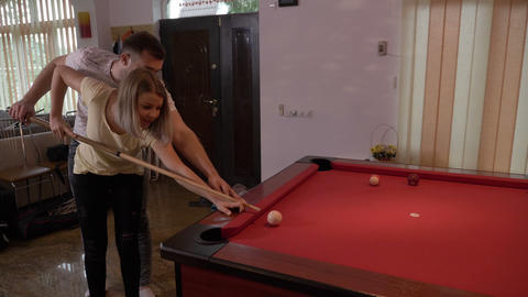 Boyfriend teaching his girlfriend to play pool flirting and having fun Footage