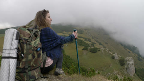 Millennial woman on mountain excursion standing high on cliff looking the Footage