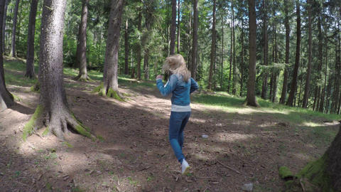 Scared young girl running away to escape from danger through mountain forest Footage