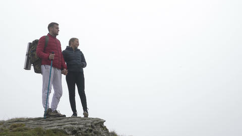 Teenage hiking couple in love kissing on the top of foggy mountain admiring the Footage
