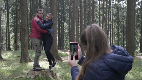 Teenage woman taking photos with her smartphone camera to a young couple hiking Footage