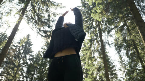 Cute young woman breathing deeply the fresh air of the forest feeling amazing in Live Action