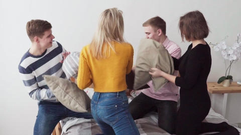 Group of happy young people fighting pillows in bedroom Footage